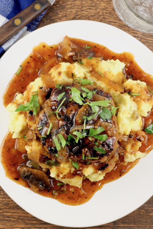 Homemade Salisbury Steak Recipe served over mashed potatoes with mushroom and onion gravy