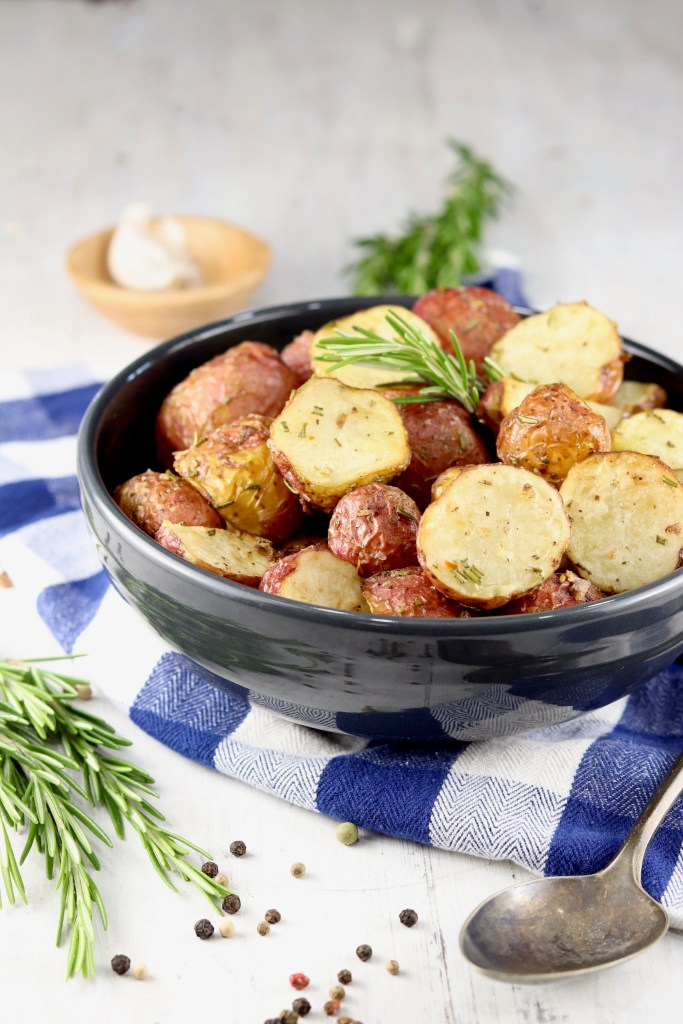 Black bowl of roasted red potatoes with rosemary