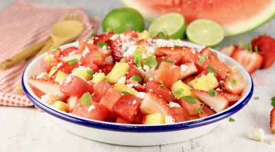 Watermelon salad in a shallow bowl with watermelon wedge and fresh limes in background