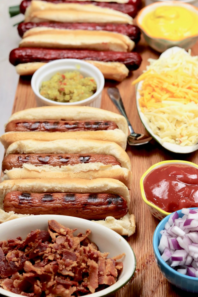 Hot Dogs on a board with bacon, onion, ketchup and shredded cheese