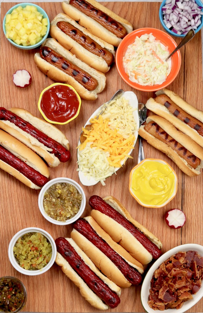 Grilled Hot Dogs with relish, bacon, mustard, slaw, and pineapples