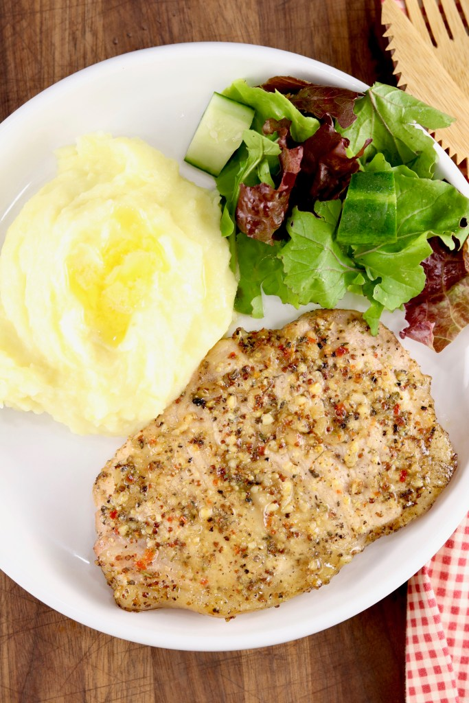 Plate of Italian Pork Chops with mashed potatoes and salad