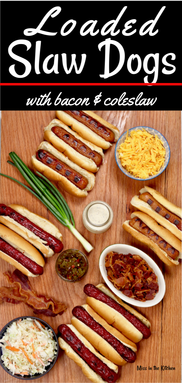 Loaded Slaw Dogs are a great addition to your summer cook out menus! Grilled hot dogs topped with smoked cheddar, bacon, creamy coleslaw and candied jalapeños