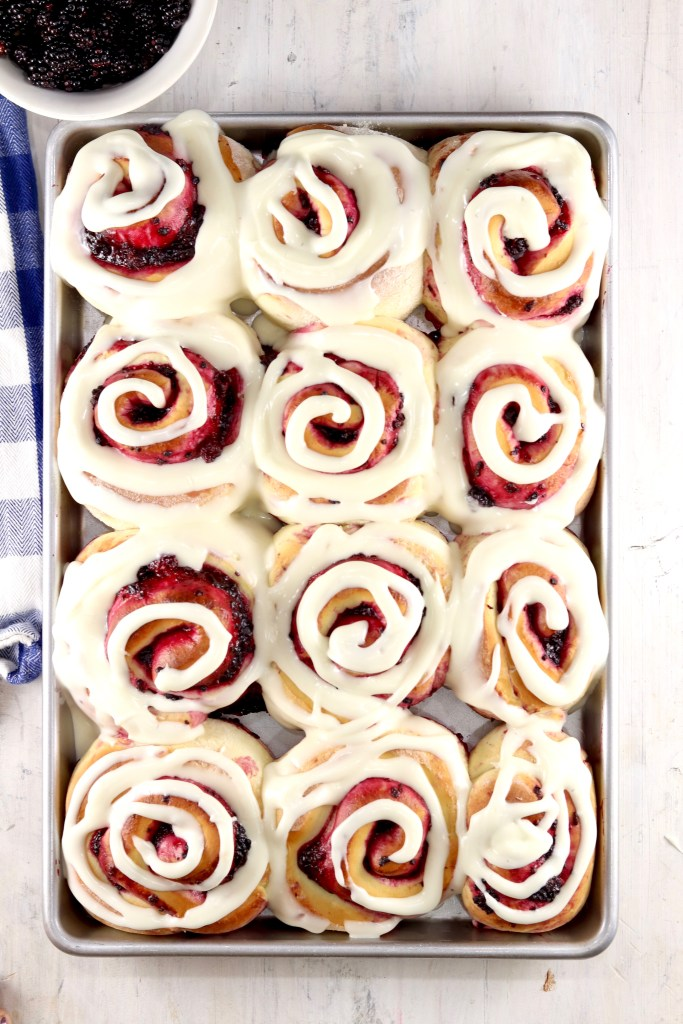 Cream cheese icing swirled over blackberry sweet rolls