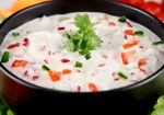 Black bowl of creamy vegetable dip garnished with cliantro