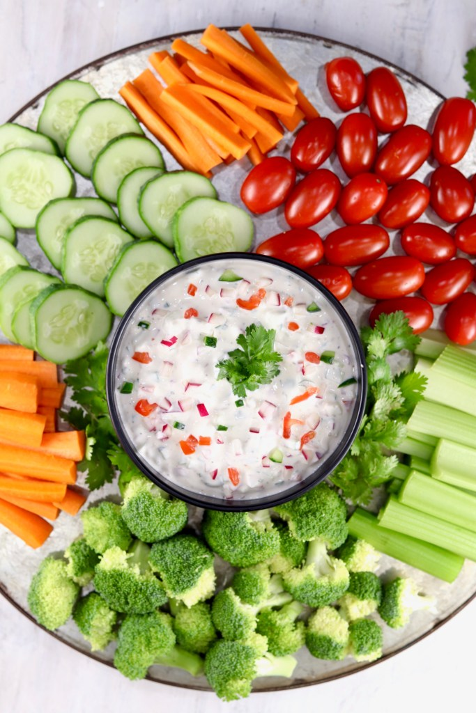 Creamy Dip with cut up carrots, cucumbers, broccoli, and grape tomatoes on a platter