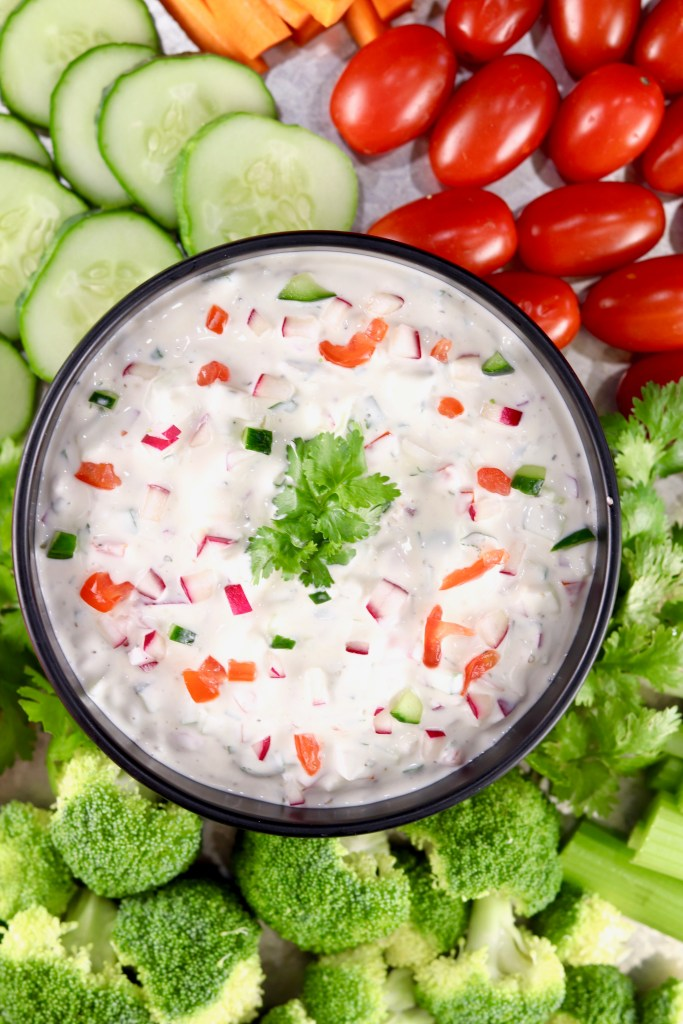 Bowl of vegetable dip surrounded by sliced vegetables for dipping