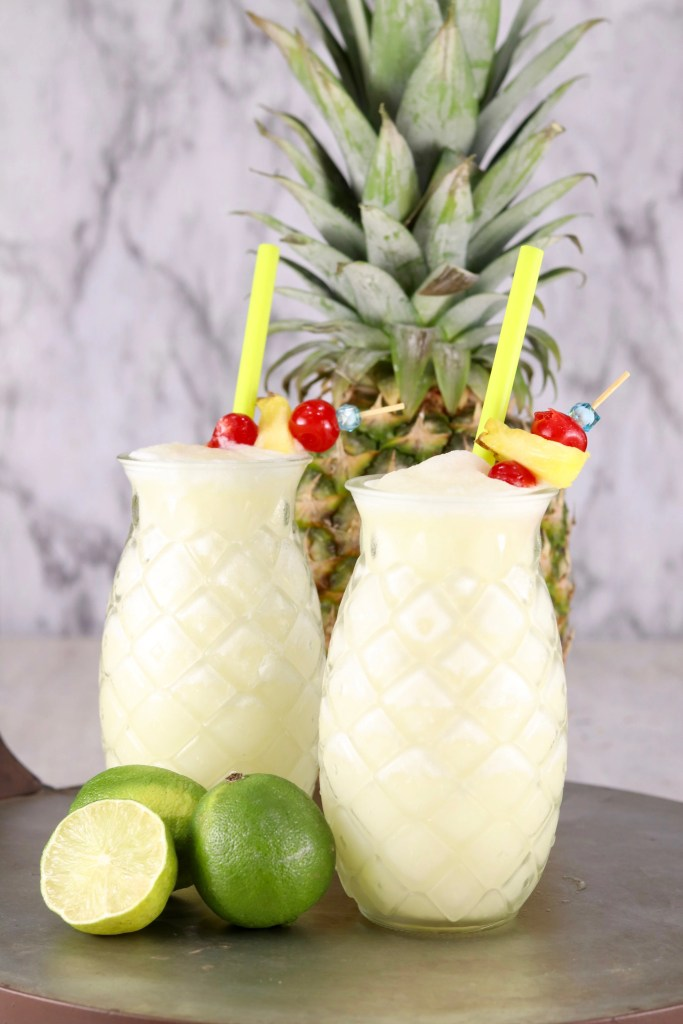 Cut glass pineapple glasses filled with pina colada mixture garnished with pineapple and cherries