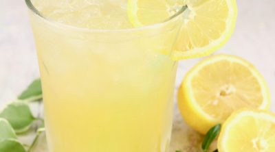 Glass of lemonade with a straw, fresh lemon and greenery beside glass