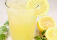 Glass of lemonade with a straw, fresh lemon and greenery beside glass