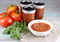 Bowl of salsa with canning jars of homemade salsa, tomatoes and cilantro