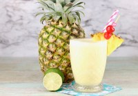 Fresh pineapple and coconut frozen drink with fresh lime and whole pineapple in background