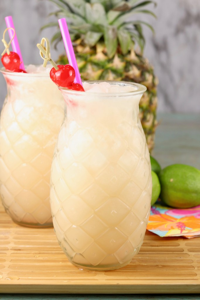 Pineapple shaped glasses with pineapple coconut wine party punch garnished with a cherry
