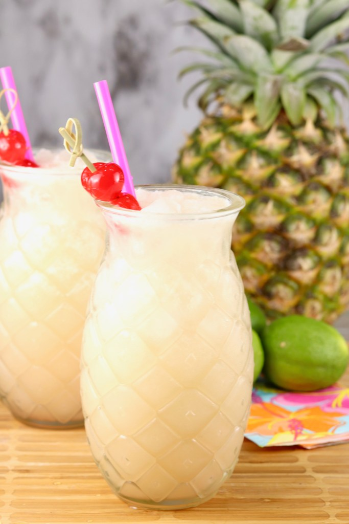 Pineapple Glass with pina colada punch garnished with a cherry and a fresh pineapple and limes in the background