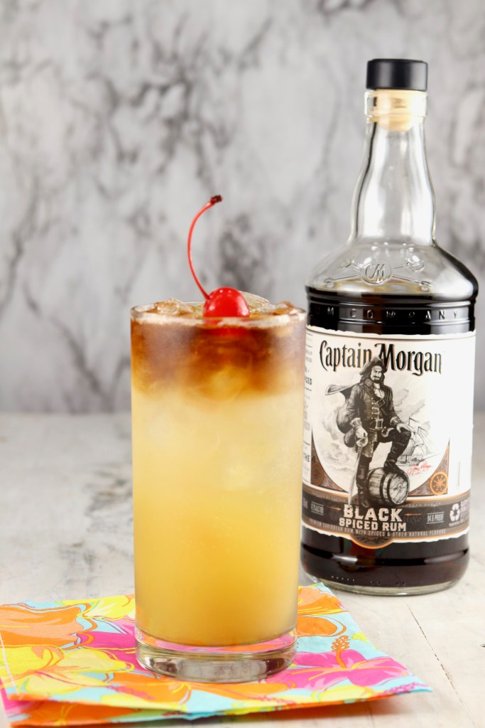 Glass of pineapple rum punch with bottle of Captain Morgan Black Rum