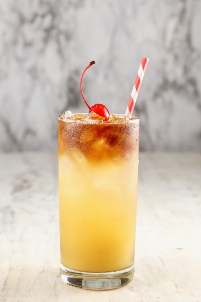 Pineapple Rum Punch with cherry and straw
