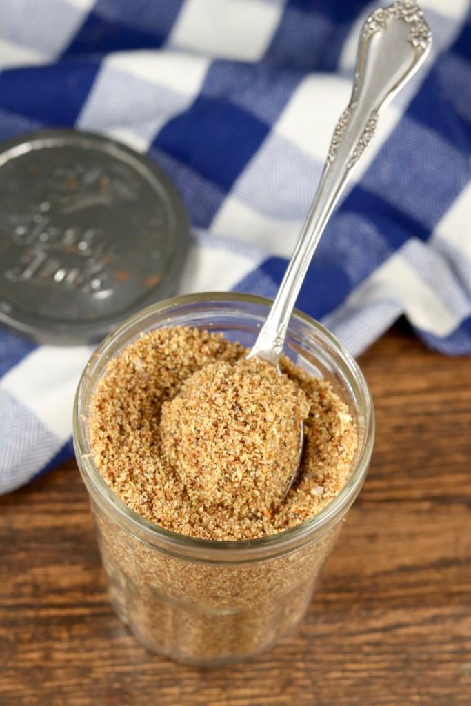 Jar of dry beef rub seasoning blend with a spoon