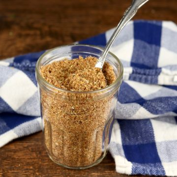 Jar of brown sugar and spices beef rub with a blue and white checked napkin