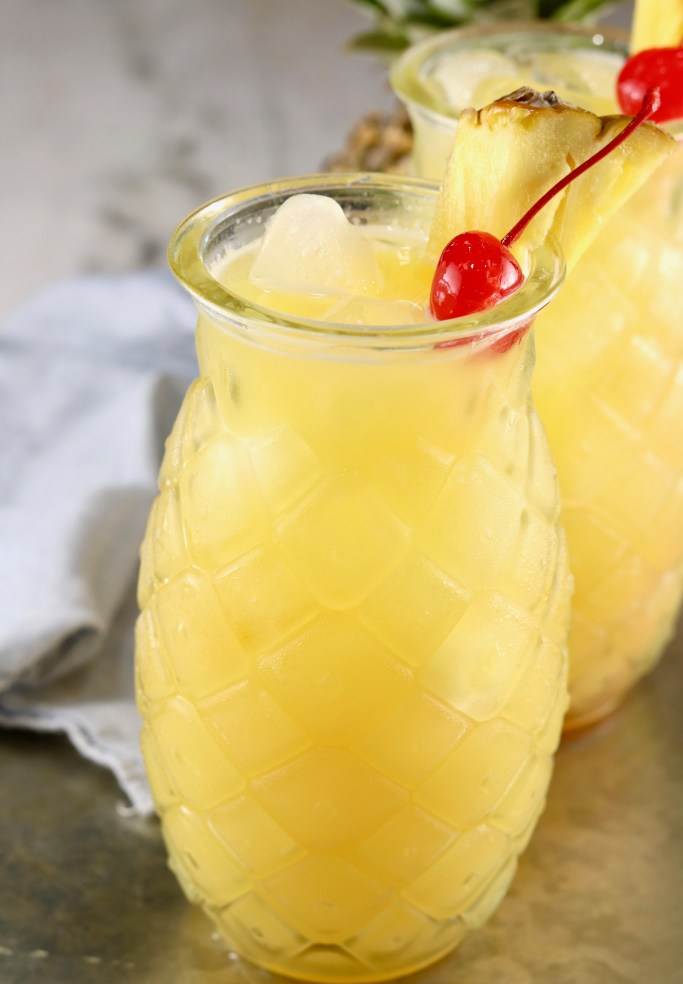 Pineapple glasses filled with peach schnapps cocktail