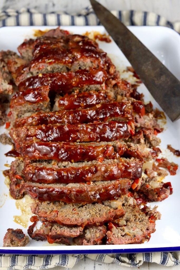 Sliced meatloaf on a white platter