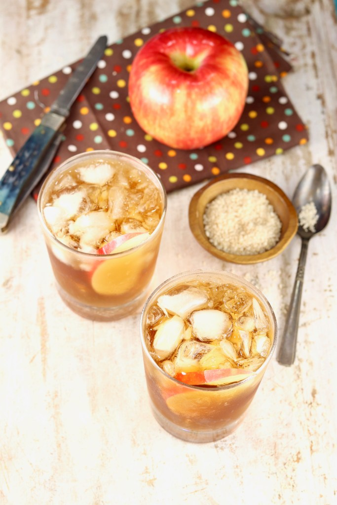 2 glasses of spiked apple cider with a fresh apple and small bowl of vanilla sugar