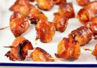 Bacon wrapped water chestnuts on a white pan