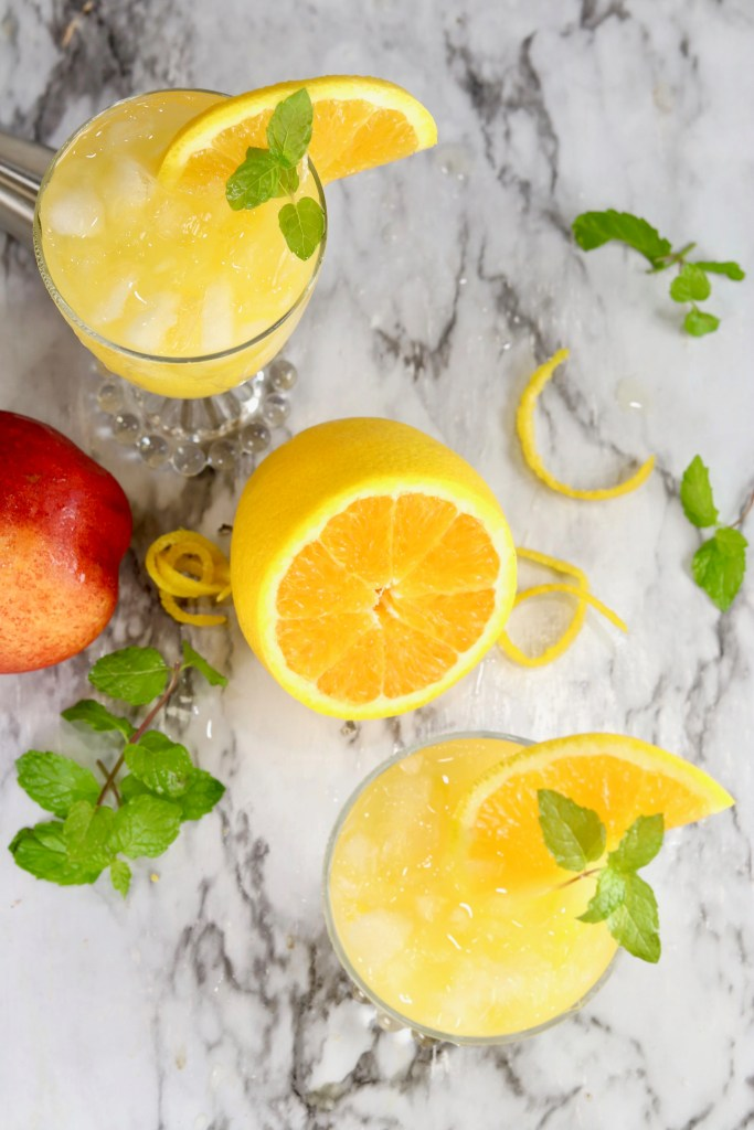 Overhead view of orange juice cocktail with mint garnish
