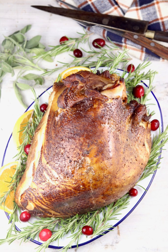 Smoked Turkey Breast on a platter with fresh rosemary and cranberries