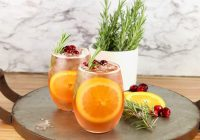 Winter wine punch in wine glasses with orange, cranberry and rosemary garnish