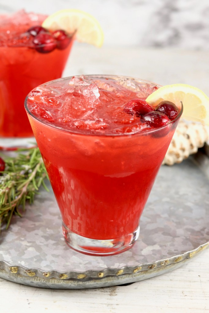 Cranberry cocktail in a cosmopolitan glass garnished with lemon