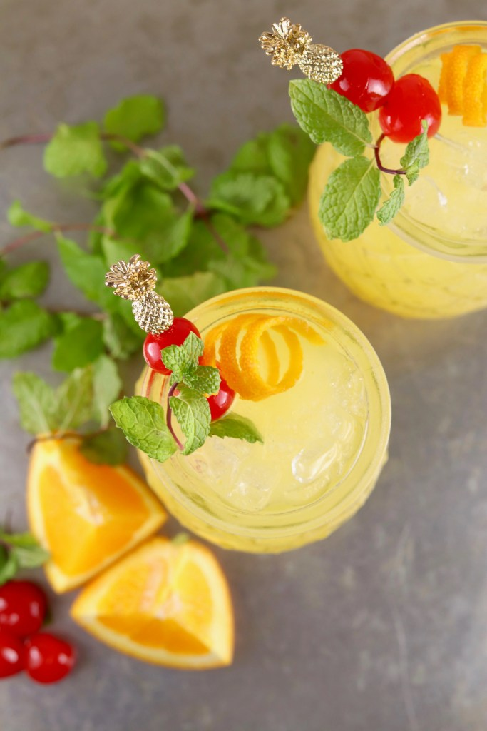 Overhead view of pineapple vodka cocktails garnished with mint and cherries