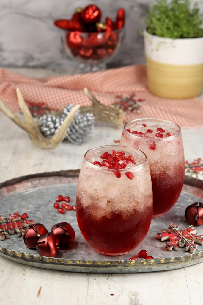 Holiday Pomegranate Mimosas on a platter with Christmas ornaments