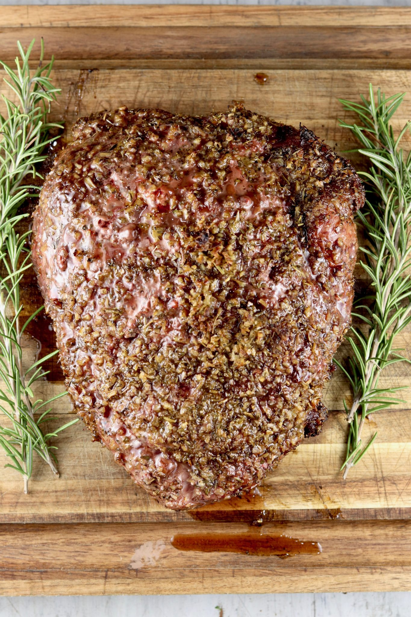 Herb Crusted roast on a cutting board with fresh rosemary