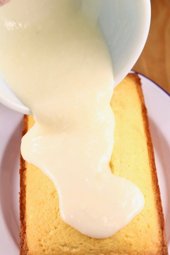 pouring buttermilk glaze over pound cake