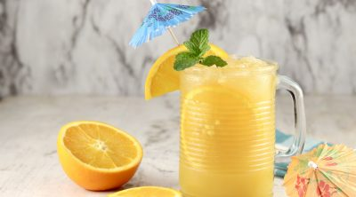 Brass Monkey Drink with orange, mint and umbrella garnish in a mug