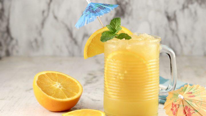 Brass Monkey Drink with orange, mint and umbrella garnish in a mug