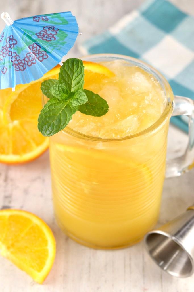 Brass Monkey Drink with orange and mint garnish + a blue drink umbrella