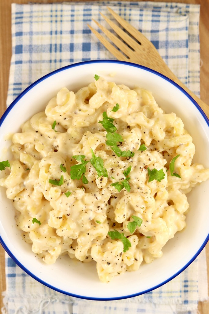 Bowl of macaroni and cheese garnished with parsley, bamboo fork