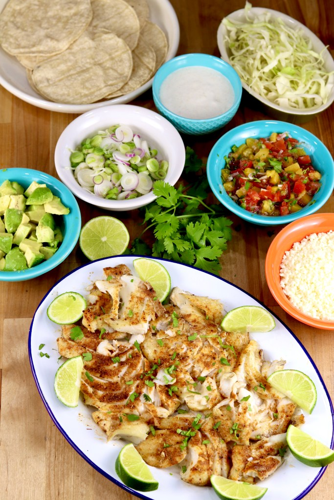 Platter of grilled fish with taco toppings and corn tortillas