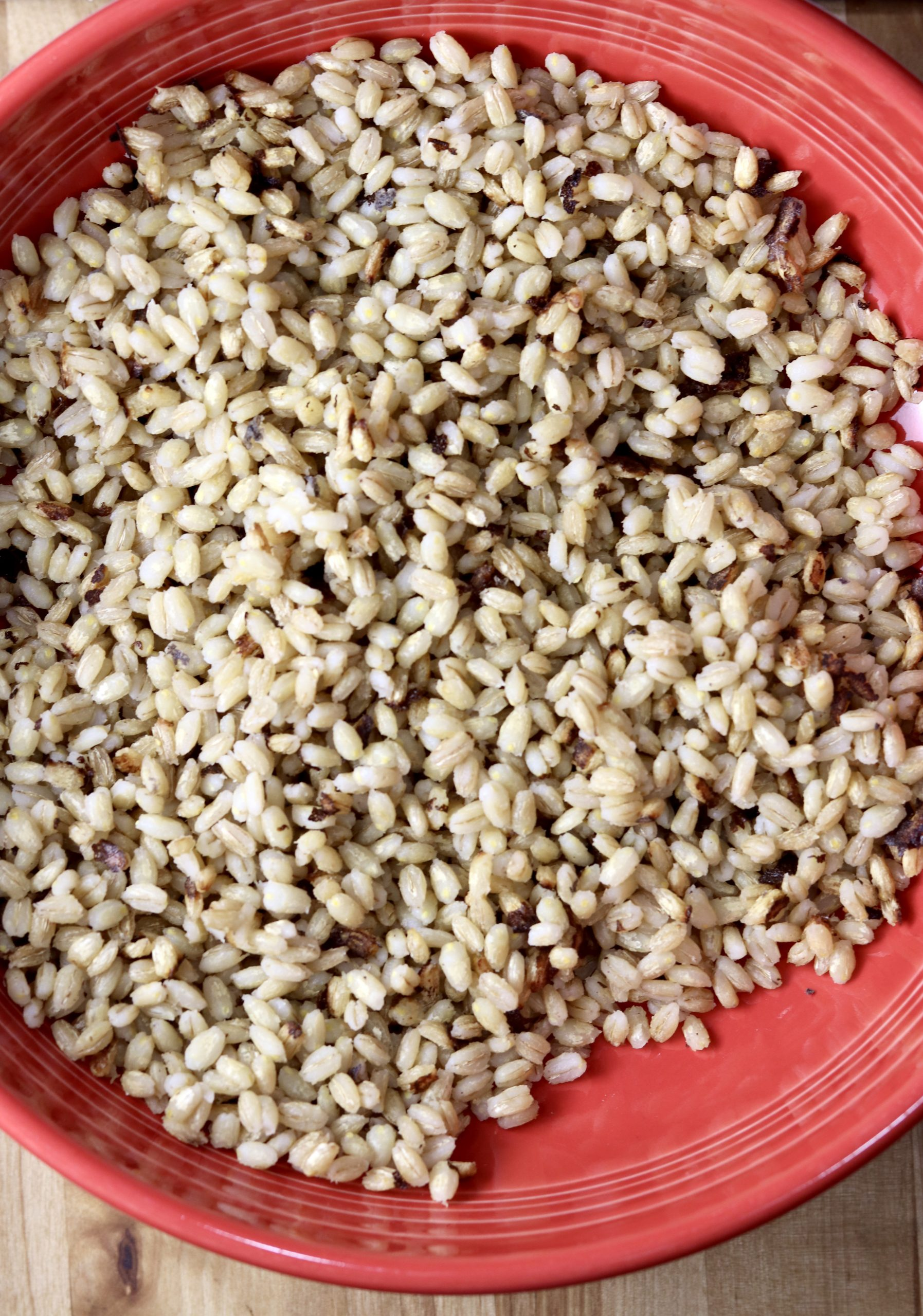 Cooked pearl barley in a red bowl
