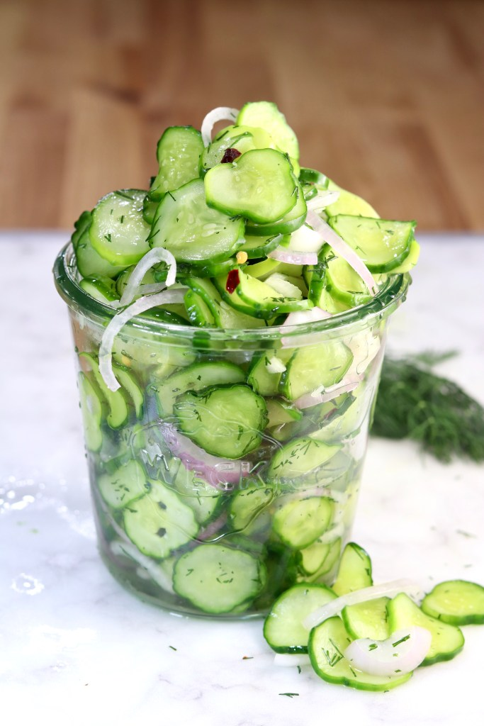 Cucumber Onion Salad in a jar on a white board