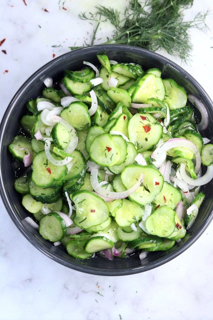 Cucumber Onion Salad with red pepper flakes in a black bowl