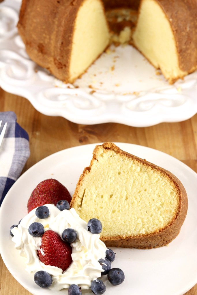 Slice of pound cake with whipped cream and berries, bundt cake in background