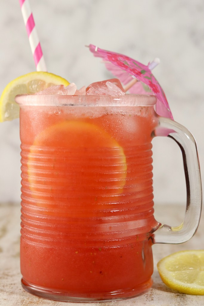 Mug of strawberry lemonade, drink umbrella, pink straw, lemon slice garnish