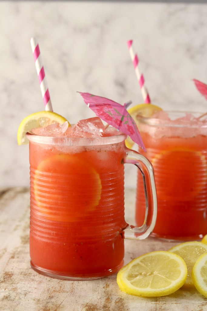 Strawberry Lemonade in 2 glasses with lemon garnish and drink umbrella