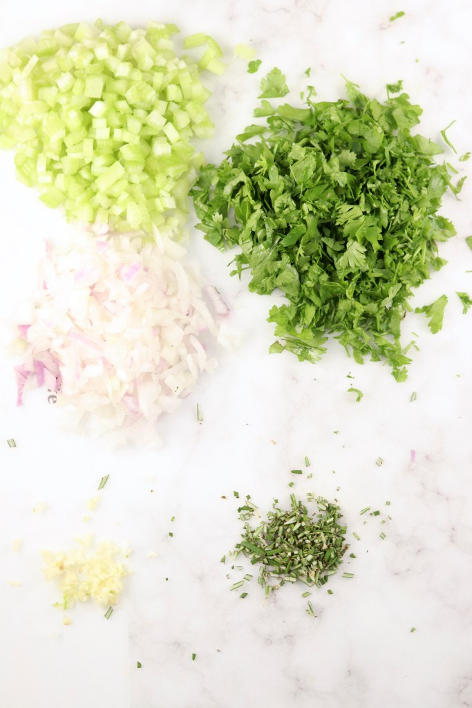 Diced celery, onion, garlic, parsley and rosemary on a light cutting board