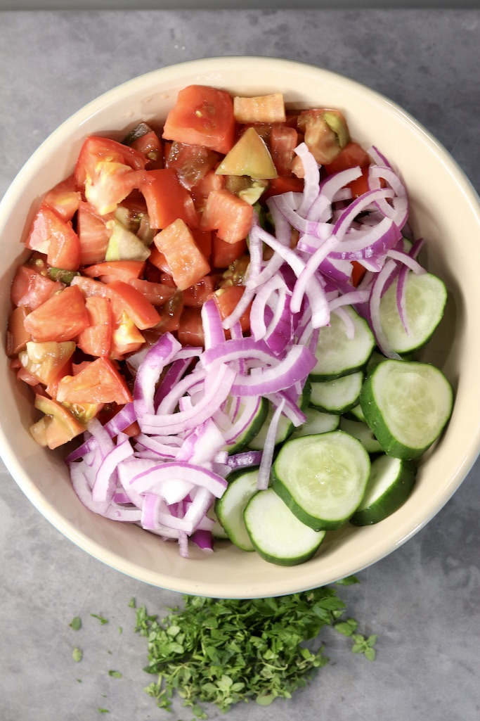 Cut up tomatoes, red onions sliced and sliced cucumbers in a bowl, fresh herbs below