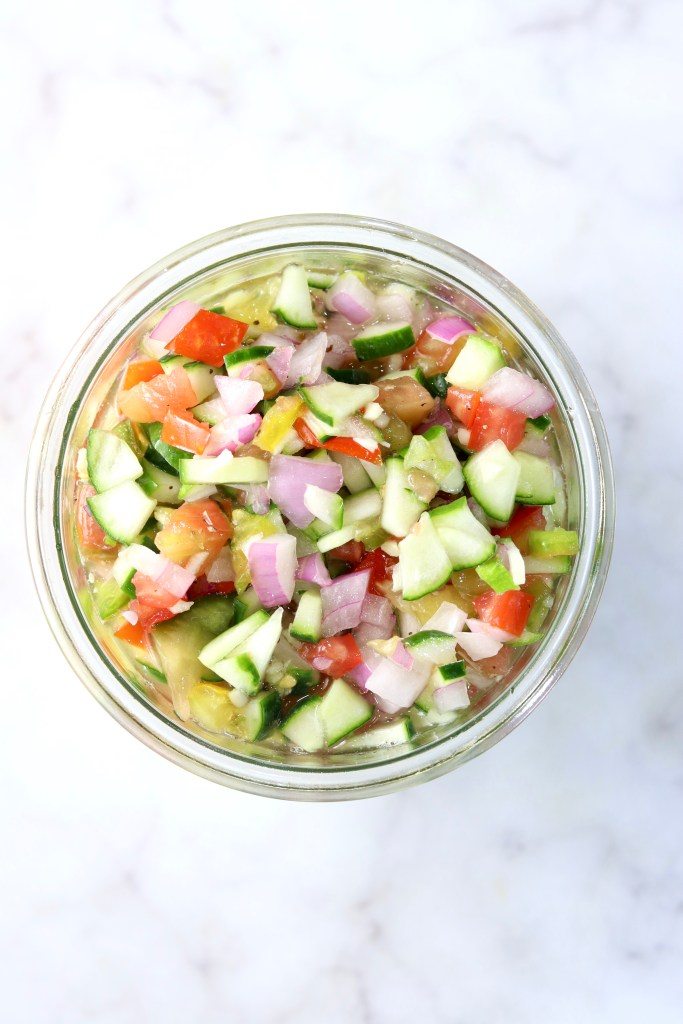 Chopped tomato, cucumber, onion salad in a jar