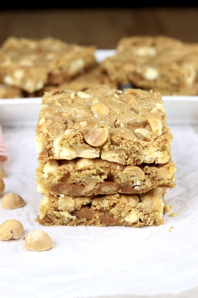 Caramel white chocolate macadamia nut bars stacked 3 on a plate