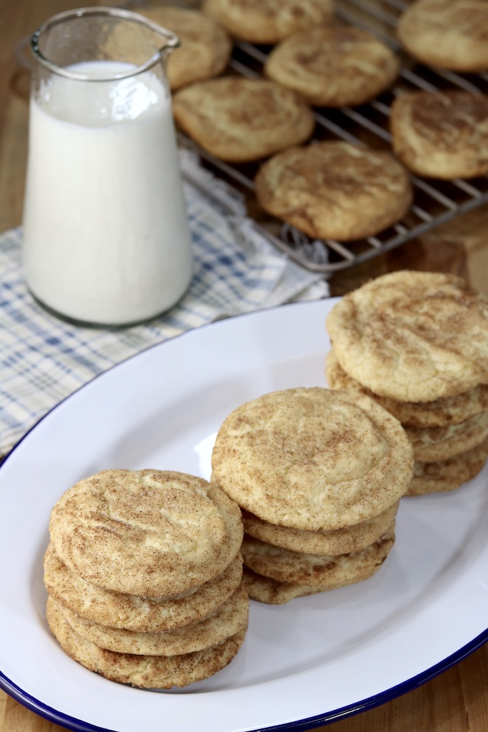 Tray of snickerdoodle cookies with small pitcher of milk behind and a cooling rack of cookies
